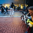 A homeless woman looks on as protesters begin to rush backwards as police announce that curfew is in effect.