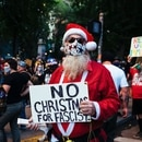 A protester wearing a Santa suit holds up a sign reading