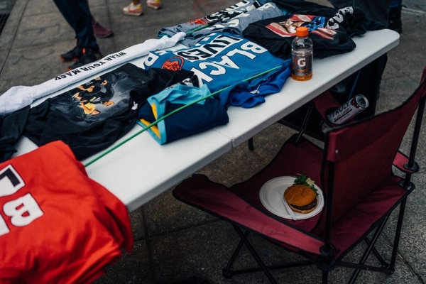 A vendor's table with T-Shirts. The vendor leaves behind a burger from Riot Ribs on July 25. (Alex Wittwer)