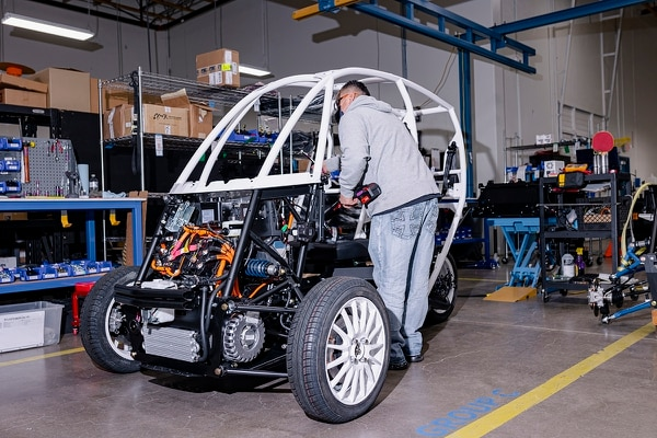 An Arcimoto employee at work on one of the company's three-wheel rigs. (Wesley Lapointe)
