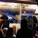 A man wearing a cross begs with rioters to leave the 4th Ave Smoke Shop, and bars the entrance. (Alex Wittwer)